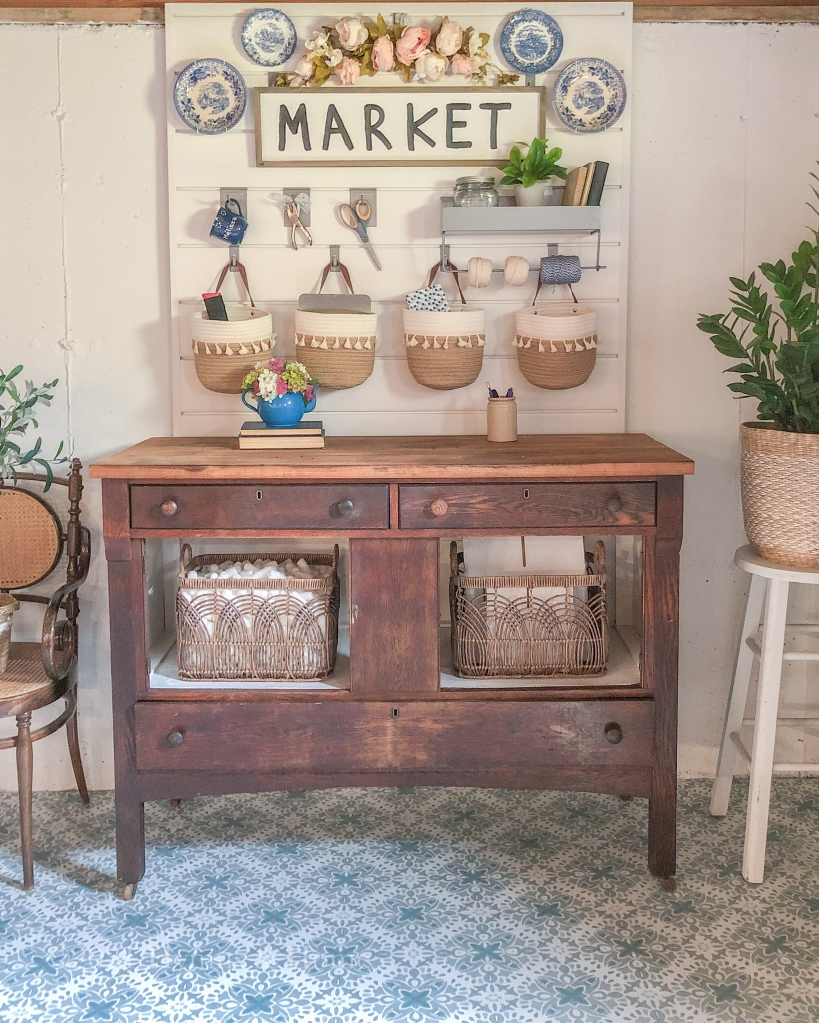 Vintage wooden work bench on top of pretty blue and white tile, white walls, farmhouse style market sign, pretty storage baskets, and plants atop vintage chair and stool.