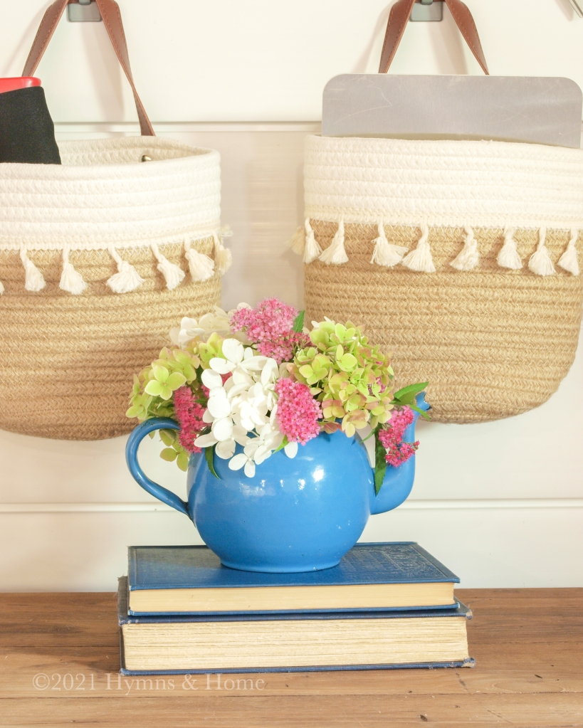 Pink, green, and white flowers in a bright blue teapot on top of a stack of vintage books