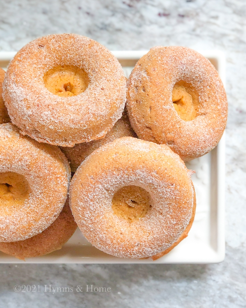Baked Fall Spice Donuts - pile of cake donuts coated in cinnamon sugar on a white ceramic tray.