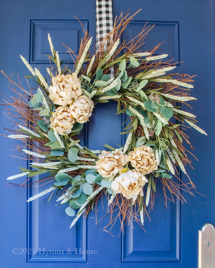 Bright blue door, neutral Fall wreath with eucalyptus, cat tails, and groups of flowers, hung with black and white gingham ribbon.