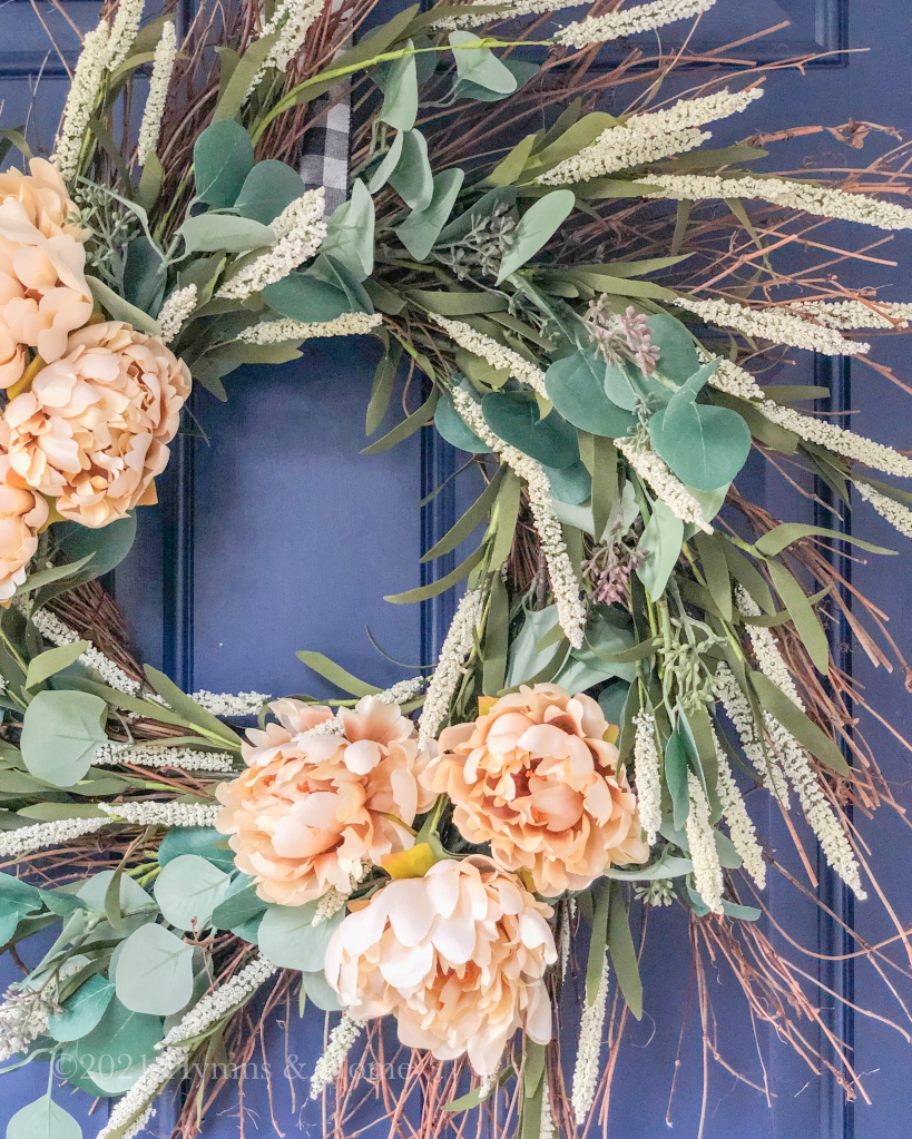 Neutral Fall wreath with eucalyptus, foxtails, and cream flowers on a blue front door