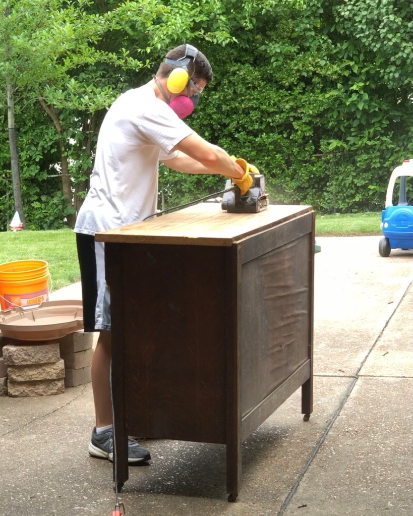 Sanding the top of the cabinet with a belt sander.