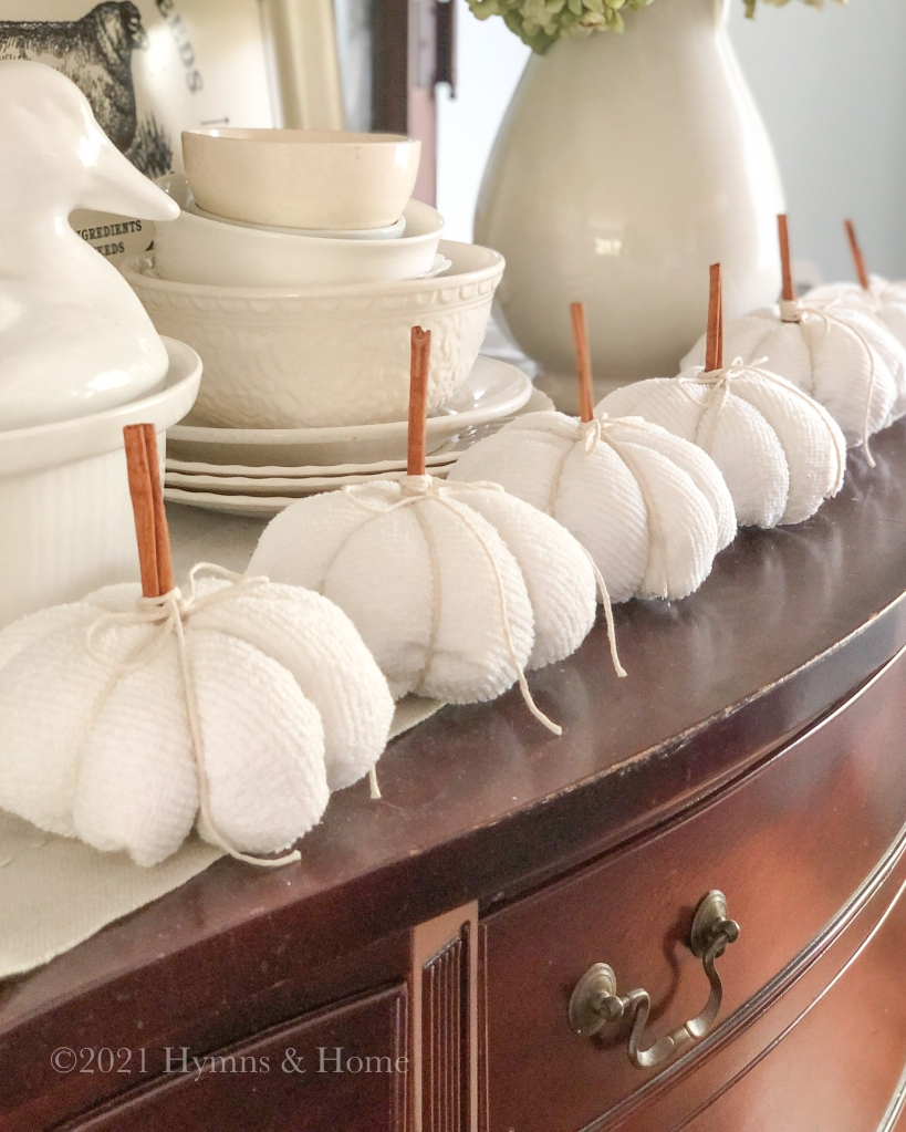 White textured pumpkins with cinnamon stick stems and twine bows on top of a vintage wooden sideboard surrounded by vintage white ironstone